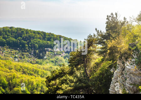 Mountain with a steep rocky slope and valley with thick green forest below in the light of the sunshine. Residential buildings and the sea are visible - Stock Photo