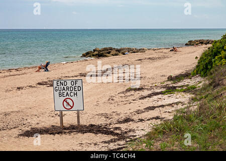 West Palm Beach, Florida - A sign warns that no lifeguards are provided beyond a sign on the beach along the Atlantic Ocean. - Stock Photo