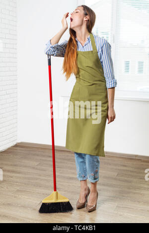 Young woman cleaning floor in room - Stock Photo