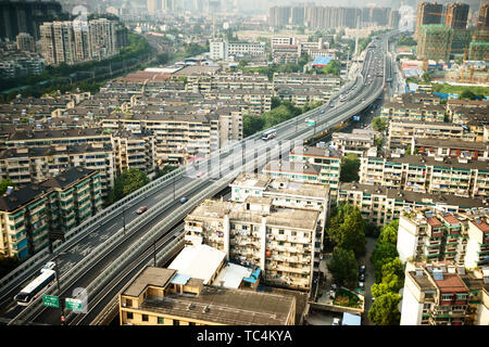 busy traffic on viaduct among modern skyscrapers - Stock Photo