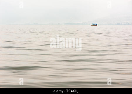 Small boat on a lake in the haze with mountains in the background,Xichang,China - Stock Photo
