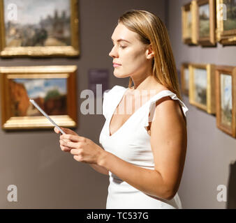 Portrait of attractive girl with guide brochure looking at paintings in art museum - Stock Photo