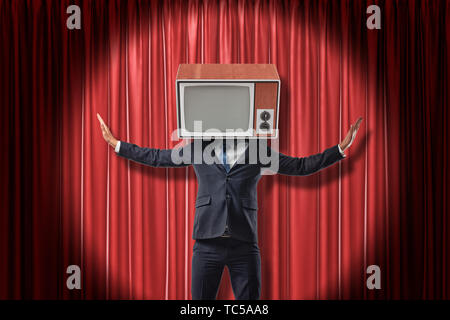 Businessman with vintage tv set instead of head raising arms on red stage curtains background - Stock Photo