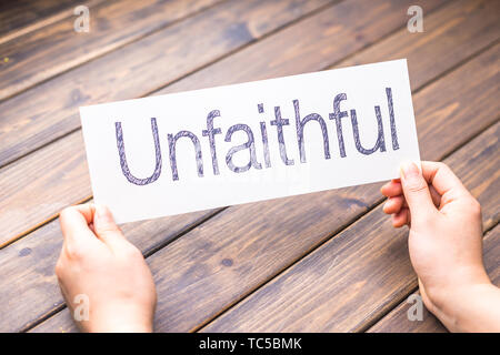 hands hold white paper with word unfaithful - Stock Photo