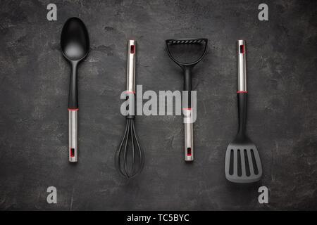 Modern Black Plastic Kitchen Utensils on Dark Background - Stock Photo