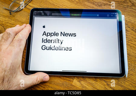 Paris, France - Mar 27, 2019: POV personal perspective on Apple News webpage seen on modern iPad Pro tablet featuring Identity guidelines - Stock Photo