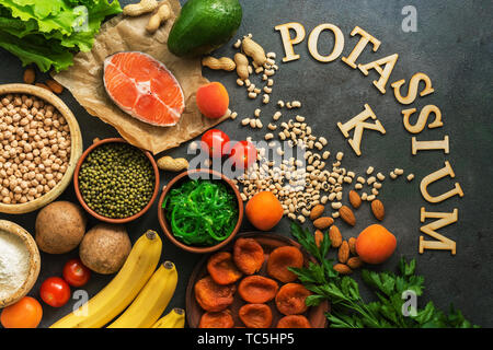 Food rich in potassium, salmon, legumes, vegetables, fruits, nuts on a dark background. Healthy food concept, avitaminosis prevention. Top view, flat  - Stock Photo