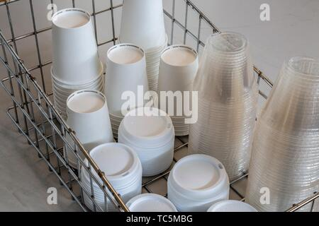 Stacks of plastic and paper cups and lids in a metal container. - Stock Photo