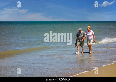 Happy elderly couple paddling in shallow sea water on sandy beach along the coast in summer - Stock Photo