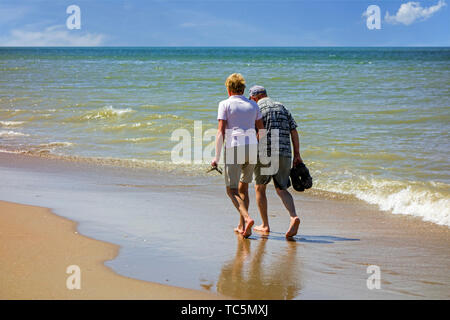 Elderly couple paddling in shallow sea water on sandy beach along the coast in summer - Stock Photo