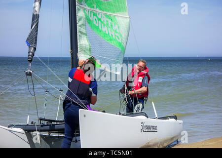 Two sailors preparing Hobie Cat, small sailing catamaran on the beach along the North Sea coast - Stock Photo