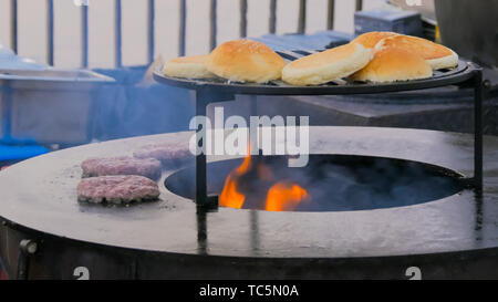 Process of preparing burgers at street food festival - Stock Photo