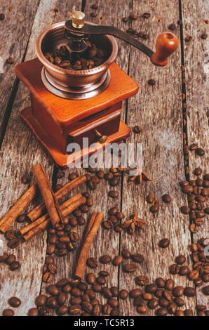 Coffee grinder with coffee beans and spices and spices cinnamon sticks, star anise on a wooden background - Stock Photo
