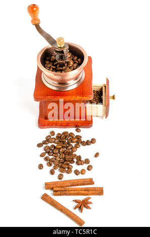 Coffee grinder with coffee beans and spices and spices cinnamon sticks, star anise on white background. - Stock Photo