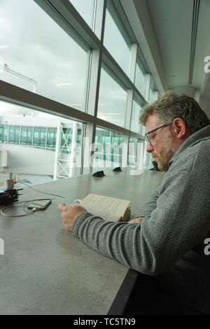 Man Reading Book and Charging Phone, JFK Airport, Queens, New York. - Stock Photo