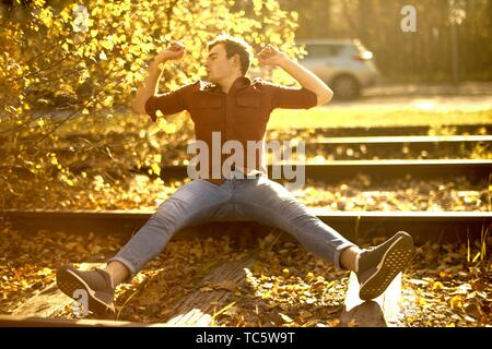 Young man stretching arms outdoors sitting on rails autumn in city, freedom, tired, joy, relaxing, chilling, Munich, Germany - Stock Photo