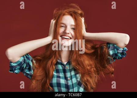 Happy beautiful girl in checkered shirt smiling at the camera while touching her red silky hair over red background. Front view - Stock Photo