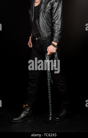 cropped view of man standing and holding metallic chains on black - Stock Photo