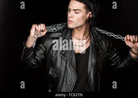 serious man looking at metallic chains isolated on black - Stock Photo