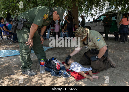 U.S. Fish and Wildlife Service Officers assist with medical aid for an infant after a group of illegal migrants from central America that crossed the Rio Grande River May 31, 2019 near McAllen, Texas. The faces are obscured by the Border Patrol to protect their identity. - Stock Photo