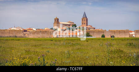 View across fields to to remains of the walls of Madrigal de las Altas Torres, Avila Province, Castile and Leon, Spain.  The church on the left is San - Stock Photo