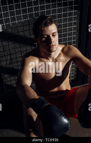 High angle view of tired boxer in black gloves sitting on floor - Stock Photo