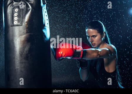 Strong boxer in red boxing gloves training under water drops on black - Stock Photo