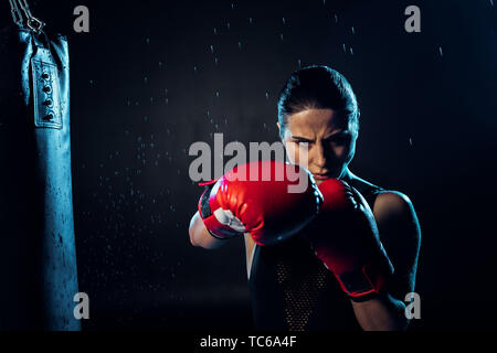 Concentrated boxer in red boxing gloves standing under water drops on black - Stock Photo
