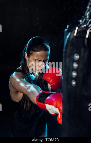 High angle view of pensive boxer in red boxing gloves training under water drops on black - Stock Photo
