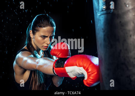 Pensive boxer in red boxing gloves training under water drops on black - Stock Photo