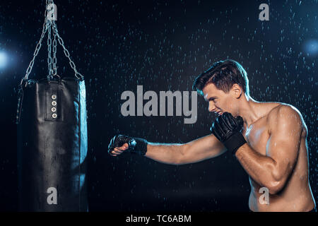Boxer training with punching bag under water drops on black - Stock Photo