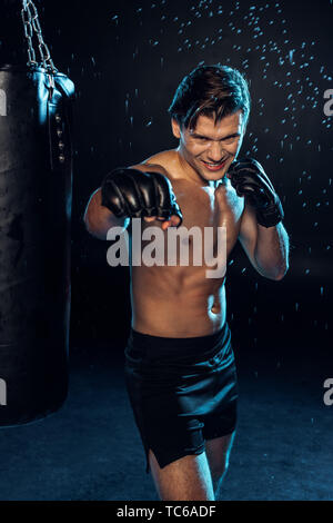 Smiling boxer in gloves standing near punching bag under water drops on black - Stock Photo