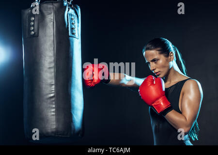 Tired boxer in red boxing gloves training with punching bag on black - Stock Photo