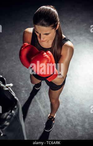 High angle view of boxer in red boxing gloves training with punching bag - Stock Photo