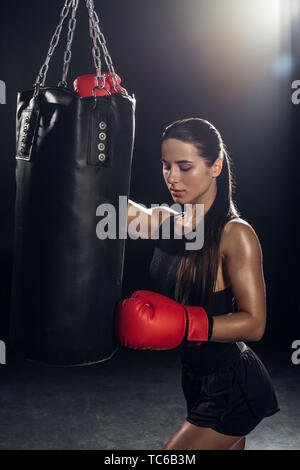 Female boxer in red boxing gloves training with punching bag - Stock Photo