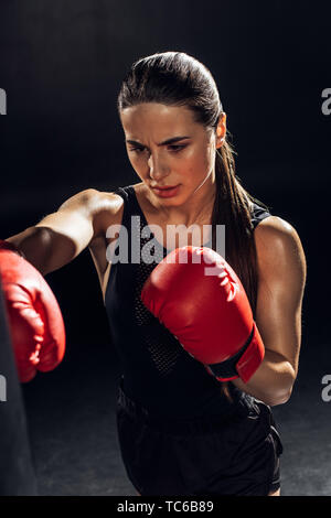 High angle view of tired boxer in red boxing gloves training with punching bag on black - Stock Photo