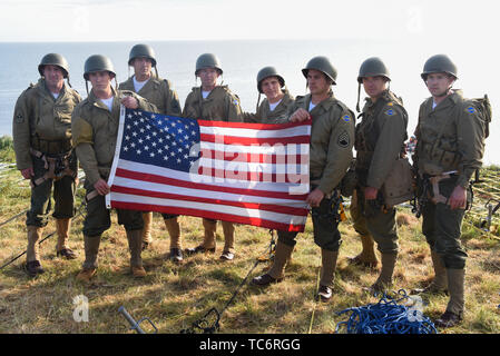 Pointe Du Hoc, France. 05th June, 2019. U.S. Army soldiers with 75th Ranger Regiment hold up an American flag after they scaled the cliffs at Omaha Beach, re-enacting Operation Overload during the World War Two D-Day invasion June 5, 2019 in Pointe du Hoc, Normandy, France. Thousands have converged on Normandy to commemorate the 75th anniversary of Operation Overlord, the WWII Allied invasion commonly known as D-Day. Credit: Planetpix/Alamy Live News - Stock Photo