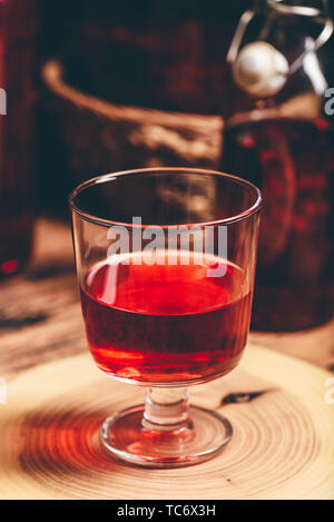 Homemade berry wine in glass on wooden surface - Stock Photo