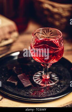 Glass of red liquor with chocolate bars on metal tray - Stock Photo