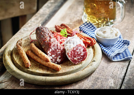 Selection of different gourmet dried spicy wild venison boar and deer sausages with mug of lager or beer served on a rustic table in a tavern - Stock Photo