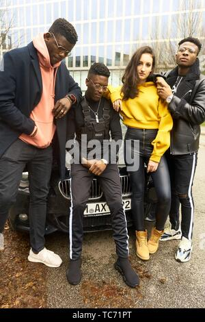 cool fashionable friends gang leaning against car in city, youth culture in Munich, Germany - Stock Photo