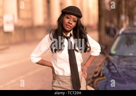 stylish woman with arms akimbo in evening sunlight at street, wearing retro outfit, business look, African Angolan descent, in city Munich, Germany. - Stock Photo
