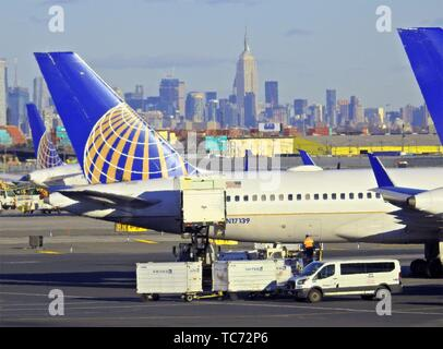 United Airlines planes at Newark (EWR) Airport. It is about 15 miles (24km) southwest of Midtown Manhattan that is seen in the background. Newark - Stock Photo