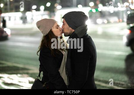 couple kissing together outdoors in city at night, in Munich, Germany. - Stock Photo