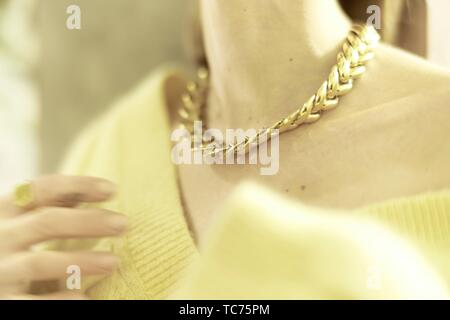 wealthy aristocratic woman wearing golden chain necklace around neck, in Munich, Germany. - Stock Photo