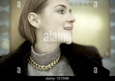 side view portrait of noble woman, wearing golden necklace, profile, in Munich, Germany. - Stock Photo