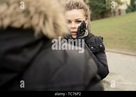 worried woman looking at counterpart, partner, relationship issue, in park, in Cottbus, Brandenburg, Germany - Stock Photo
