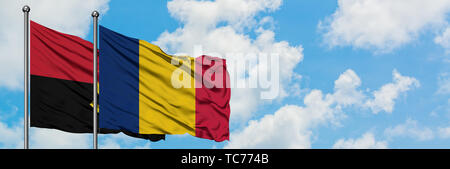 Angola and Chad flag waving in the wind against white cloudy blue sky together. Diplomacy concept, international relations. - Stock Photo