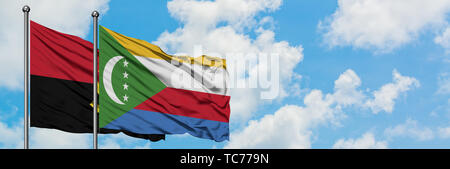 Angola and Comoros flag waving in the wind against white cloudy blue sky together. Diplomacy concept, international relations. - Stock Photo