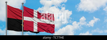 Angola and Denmark flag waving in the wind against white cloudy blue sky together. Diplomacy concept, international relations. - Stock Photo